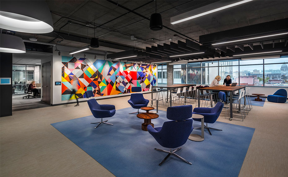 Colorful wall graphic and staff working at bar height tables in open collaboration space.